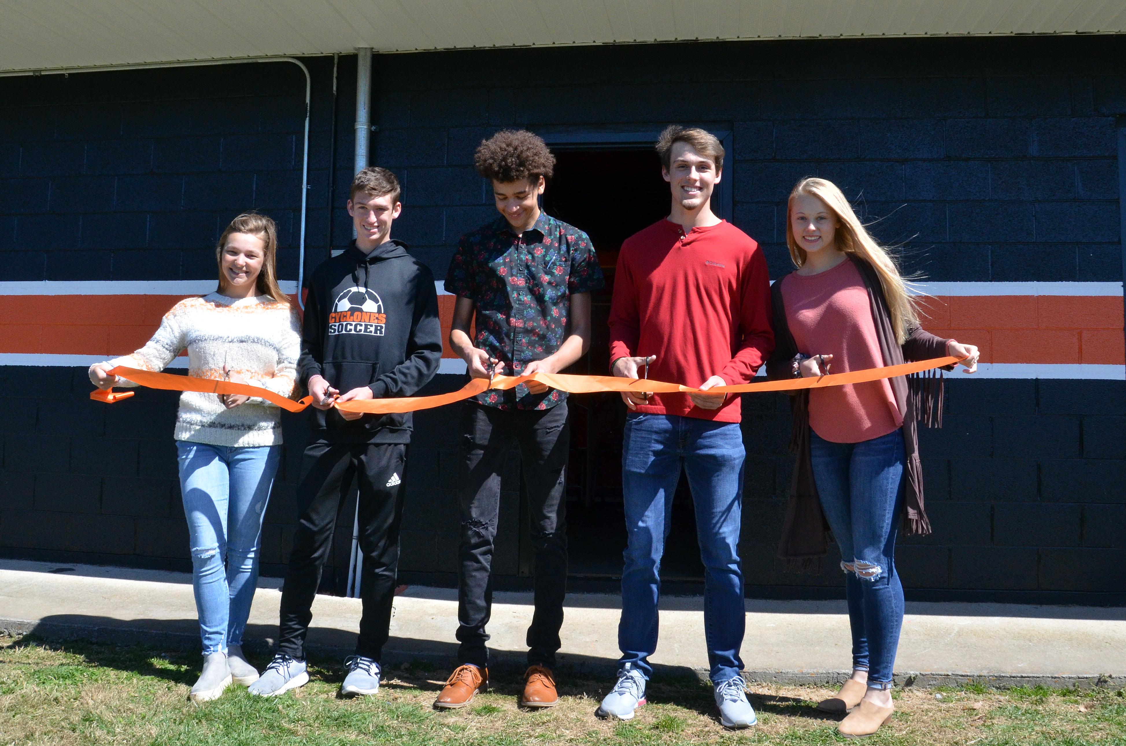 Community Improvement students (left to right) Maggie Johnson, Jaxton Holly, Nico Ashley, Evan Carter, and Kaylen Shell cut the ribbon on the new soccer locker room.